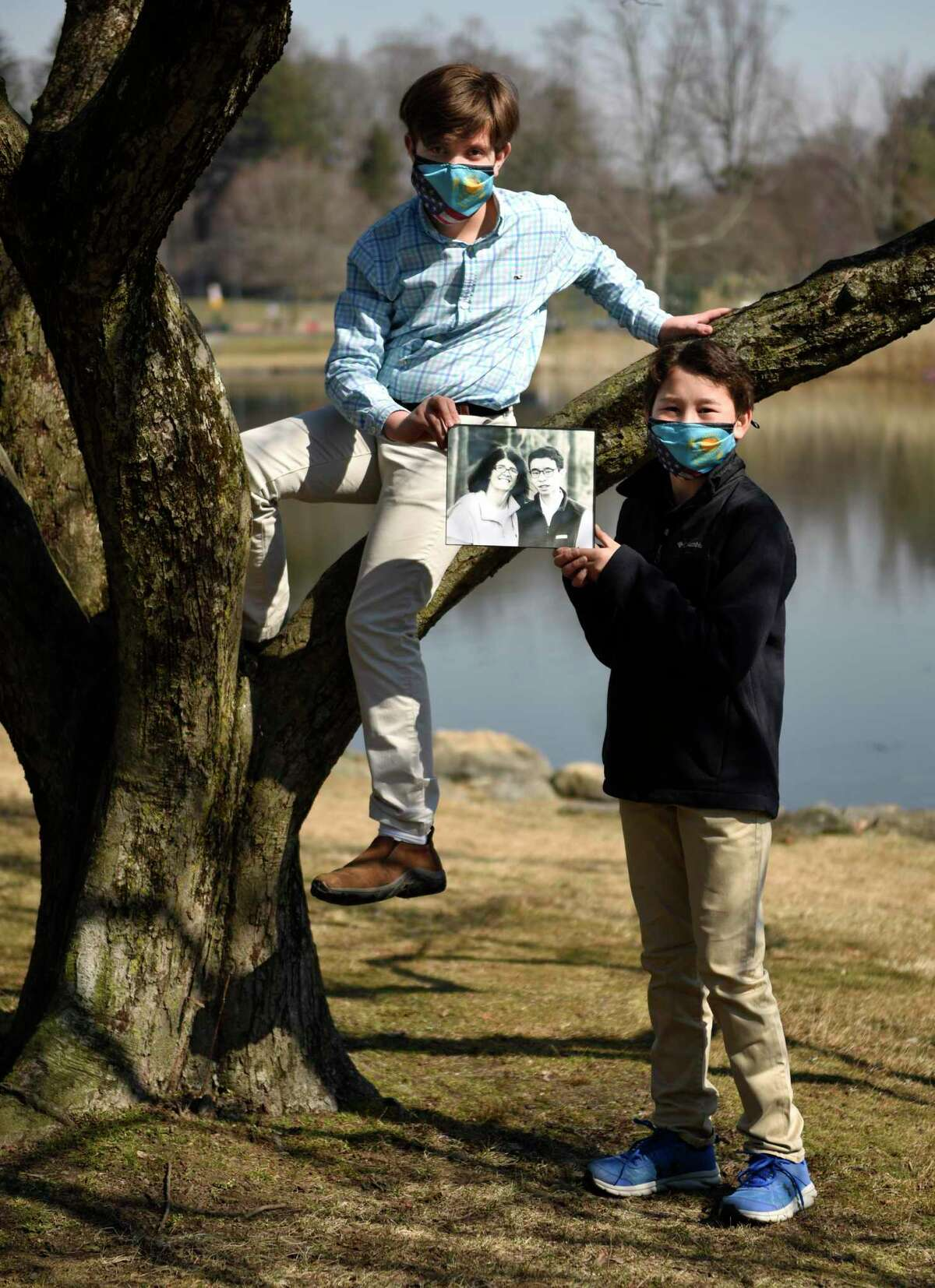 Oliver Vigale, 11, left, and Major Karp, 12, hold a photo of Carolyn Tarpey and her 14-year-old son, Henry, at Bruce Park in Greenwich, Conn. Thursday, March 11, 2021. Tarpey was diagnosed with esophageal cancer three months ago and then contracted COVID-19 in February. Carolyn is currently at Yale New Haven Hospital in a medically induced coma on a ventilator. Her friends started a GoFundMe campaign that has raised close to $100,000 to support the costs of her medical care and her 14-year-old son, Henry.