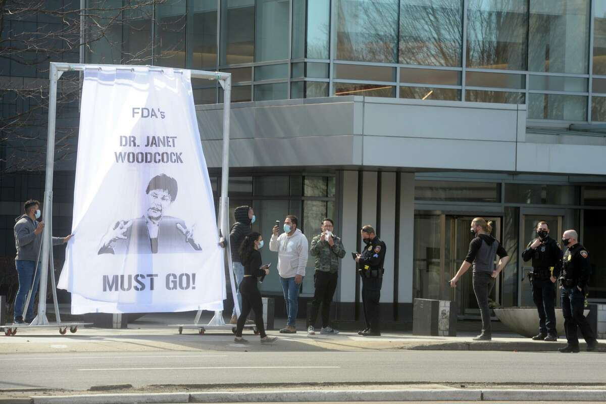 A small group of people gathered and hung a large curtain sculpture as a protest of FDA commissioner Janet Woodcock, in front of the Purdue Pharma headquarters in Stamford on Friday.