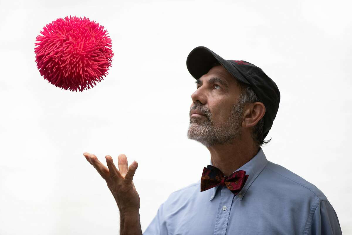Robert Siegel, a Stanford virologist, looks at a rubber ball that is shaped like the coronavirus Tuesday, March 24, 2020, in Palo Alto, Calif.