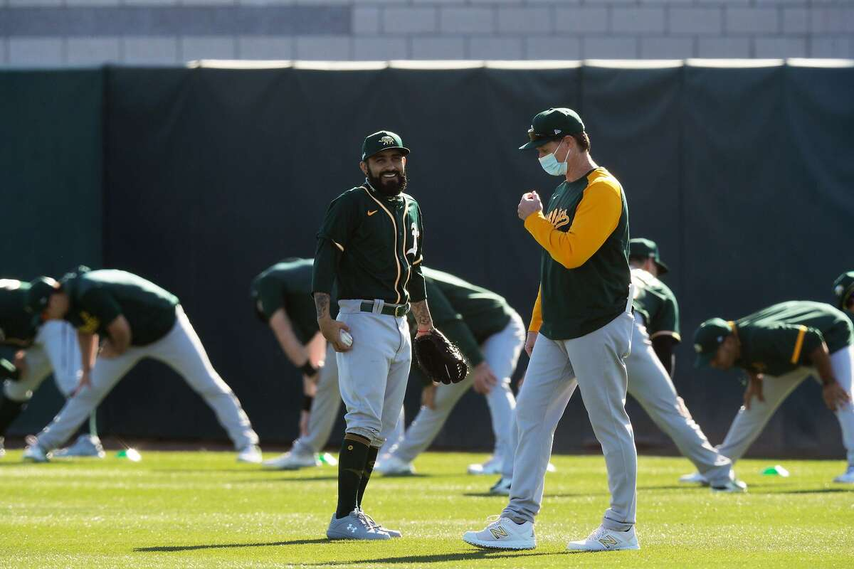 Sergio Romo (54) talks with a coach as the Oakland A's held a practice during spring training at Fitch Park in Mesa, Ariz., on Saturday, February 27, 2021.