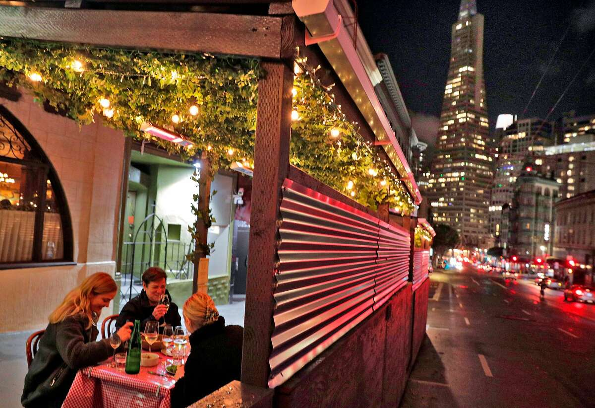 Customers enjoy dinner at Tosca Cafe where dinner service has resumed outside in San Francisco, Calif., on Wednesday, November 18, 2020. Tosca has reopened for outdoor dining with an elaborate parklet.