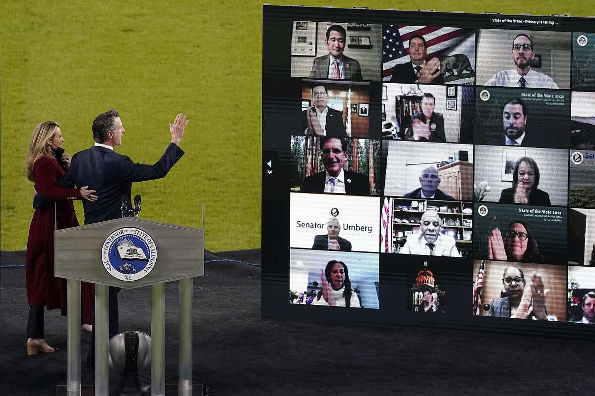 California Gov. Gavin Newsom waves to the virtual audience as he and wife Jennifer Siebel Newsom walk away from the stage after he delivered his State of the State address from an empty Dodger Stadium on Tuesday.