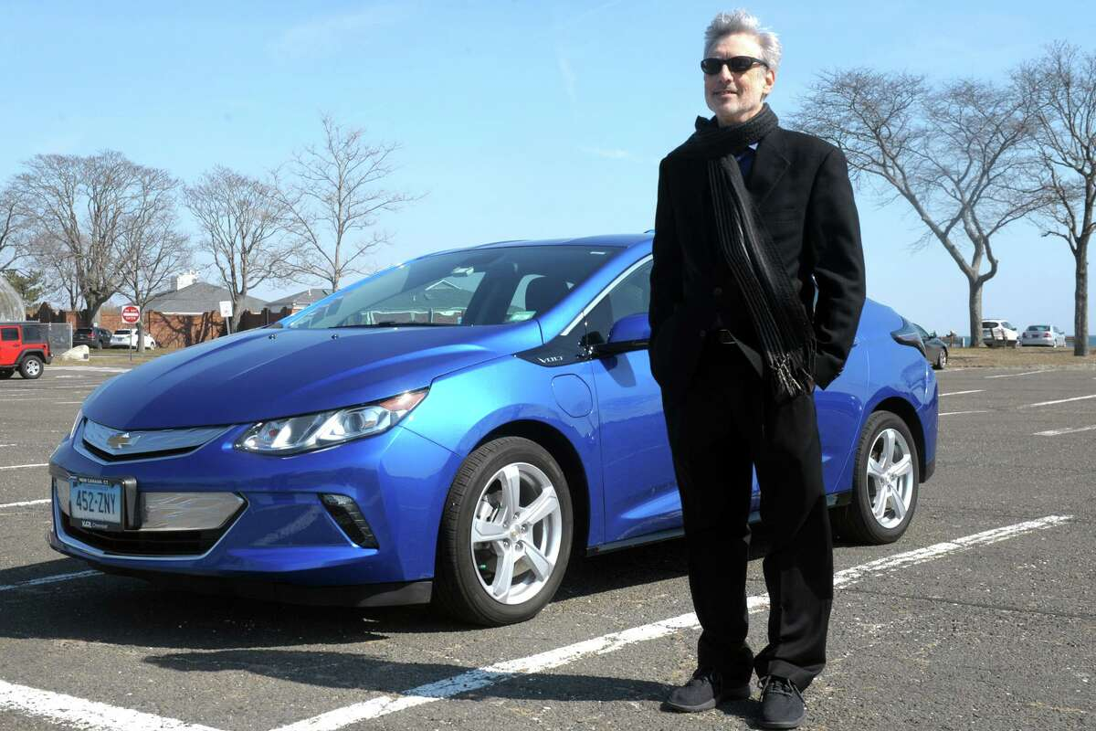 Barry Kresch, president of the EV Club of Connecticut, stands next to his 2016 Chevy Volt, at Compo Beach in Westport, Conn., on March 9, 2021. Kresch purchased the vehicle in 2015 with a rebate through the state's Connecticut Hydrogen Electric Automobile Purchase Rebate (CHEAPR) program.