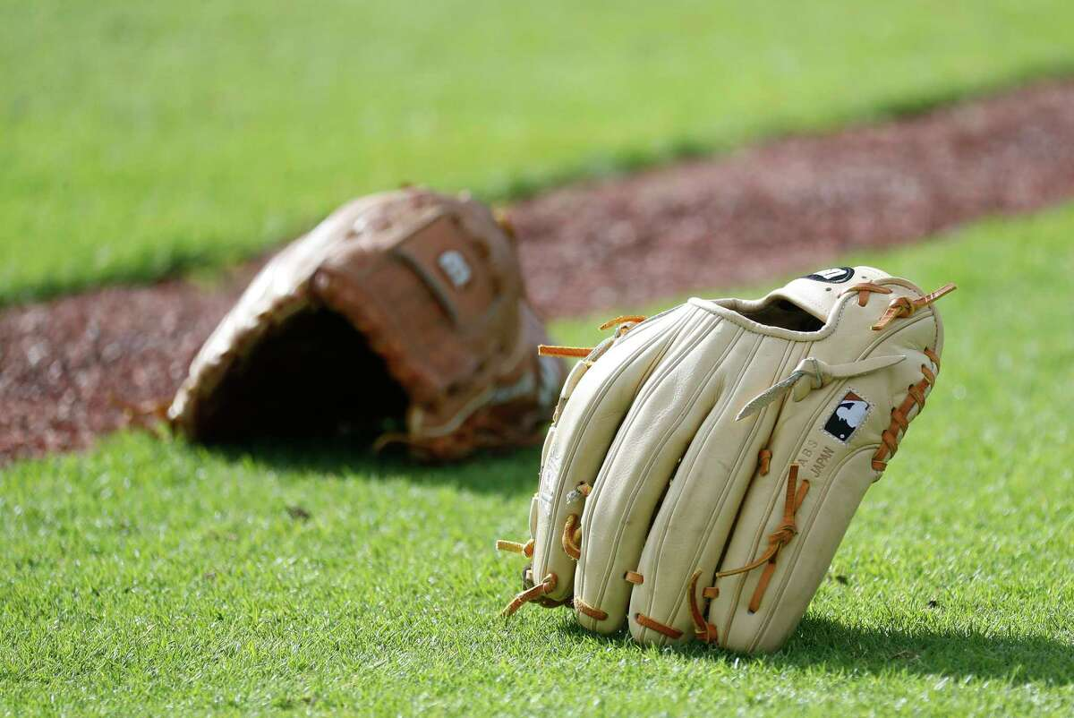 Houston Astros pitcher's gloves on the field as they warmed up during the second day of full-squad workouts for the Astros at Ballpark of the Palm Beaches in West Palm Beach, Florida, Tuesday, February 23, 2021.