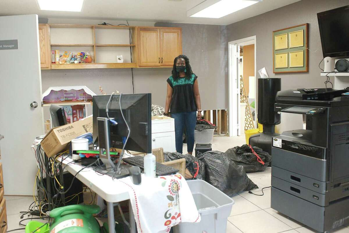 Bridge Over Troubled Waters director Olivia Rivers stands in a meeting room where salvaged items were stored after damage from the recent winter storm. The organization is seeking donations from the community to help with repairs.
