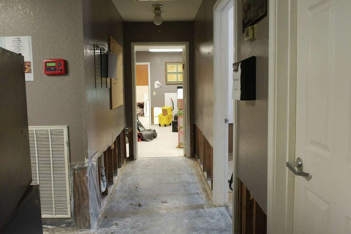 Water damage to the walls and flooring is visible in the hallway of The Bridge Over Troubled Waters' child care facility