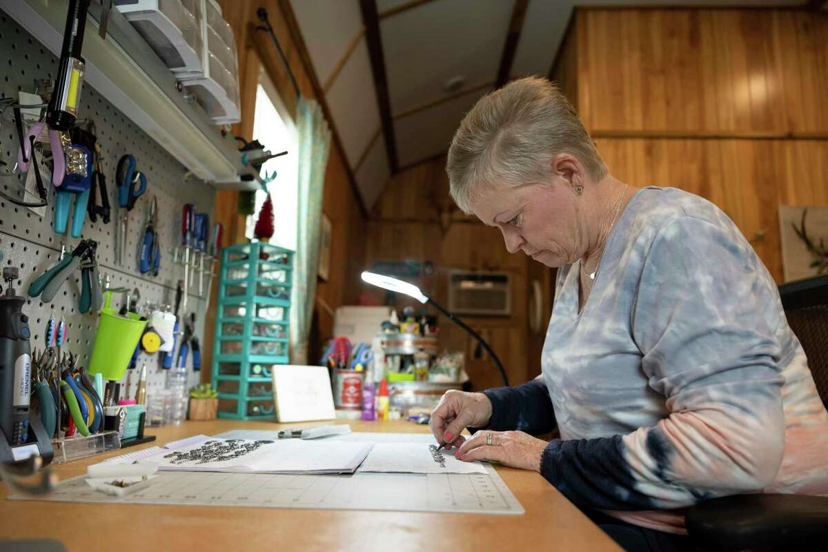 Deborah Baker, owner of Ammo Bling Queen, works on a custom jewelry piece in her work area, Wednesday, March 10, 2021, in Willis. Baker cuts and finishes all the ammunition that's used in her jewelry.