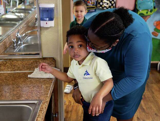 Ronisha Hill, right, helps Kion Richards, 3, tuck his shirt after he washed his hands at Creative Corner Child Development Center on Tuesday, March 9, 2021, in Houston. The pandemic has bankrupt daycares across the country, and many have had to consider closing or close all together. Pamela Humphries, who owns Creative Corner, thinks she wonít have to close any of her daycares, but says she is worried about her staff's mental health. Photo: Godofredo A. V·squez, Houston Chronicle / Staff Photographer / © 2021 Houston Chronicle