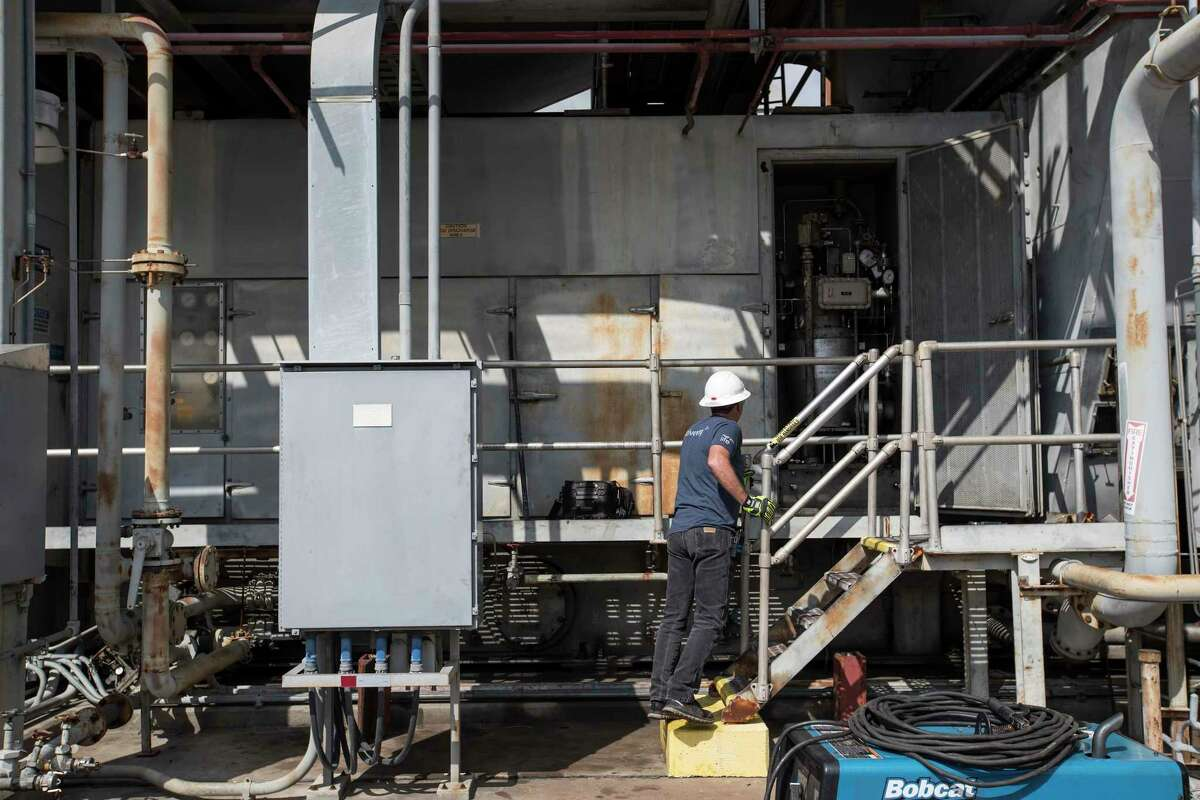 In this file photo, a worker checks on one of the systems under maintenance at NRG's TH Wharton Generating Station. Power generators have faced challenging economic conditions in recent years.