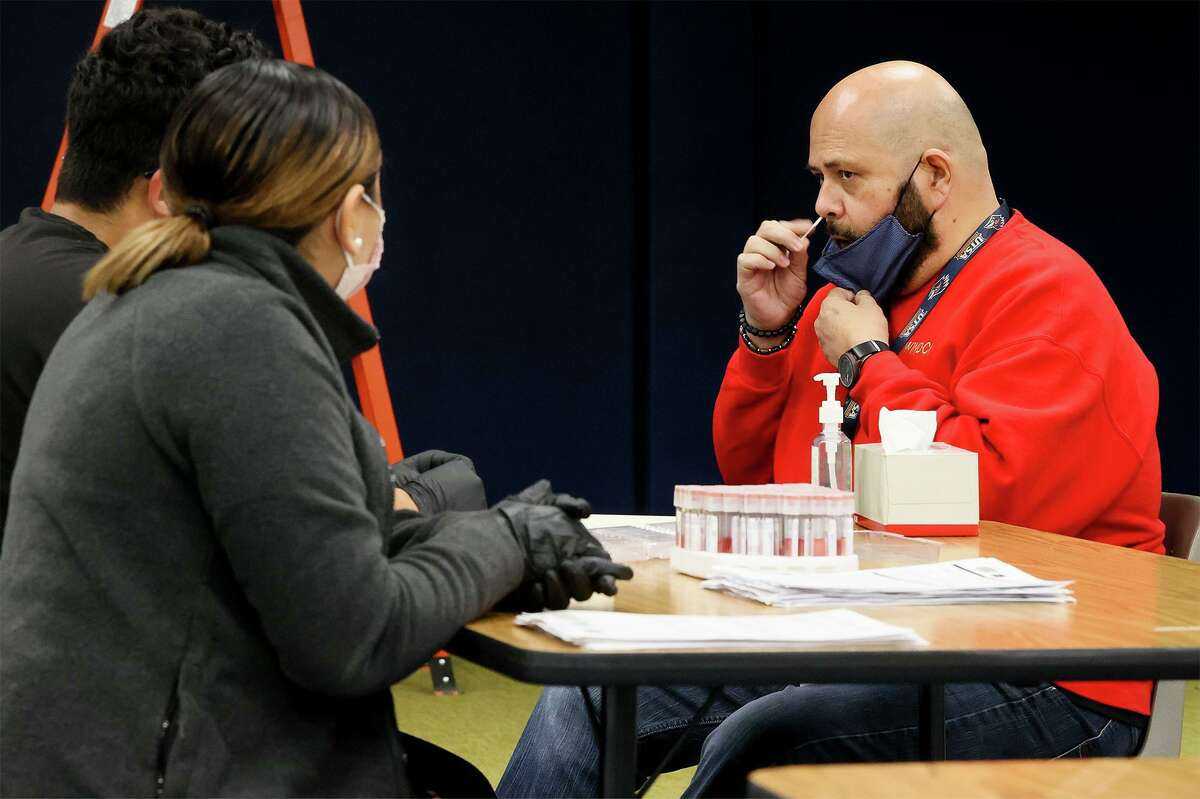 Angel Navarro, left, and Gloria Olivo with Community Labs watch as Elolf Elementary fifth grade teacher Robert Ozuna takes a self-administered COVID-19 test at the school in Converse in January.