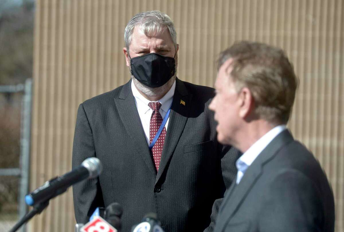 Mayor Joseph Cavo listens as Governor Ned Lamont speaks after visiting a COVID-19 vaccination clinic for staff of local child care providers at Rodgers Park School. Friday afternoon, March 12, 2021, in Danbury, Conn. Cavo is not issuing a Danbury mask mandate for now.