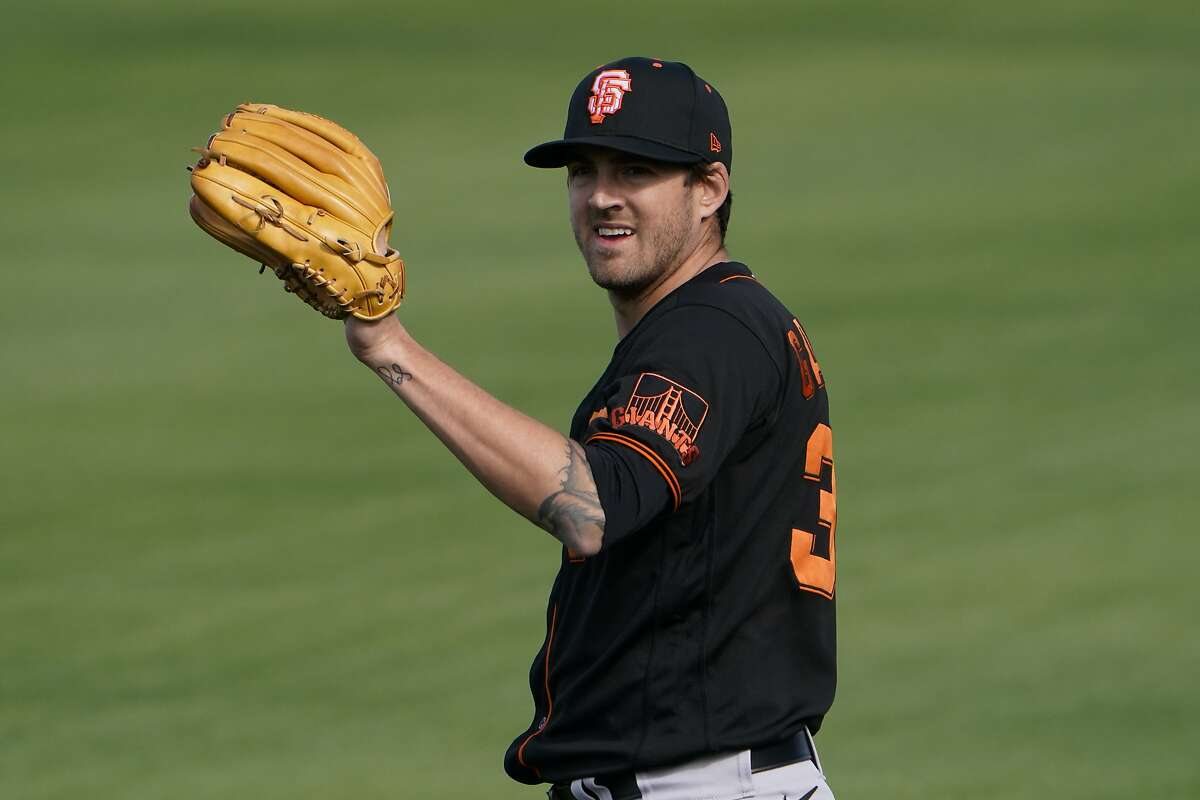 San Francisco Giants pitcher Kevin Gausman catches a ball during the team's spring training baseball workout in Scottsdale, Ariz., Friday, Feb. 26, 2021. (AP Photo/Jae C. Hong)