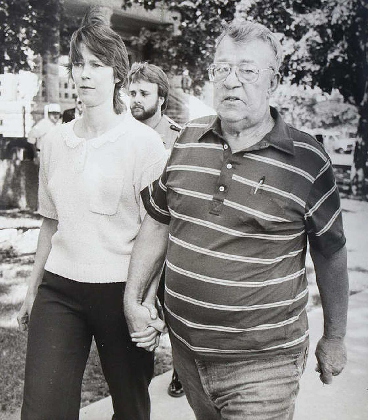 Paula Sims holds the hand of her father, Orville Blew, as they leave the Jersey County Courthouse after posting bond in May of 1989 on four felony charges related to the death of her first daughter, Loralei Marie Sims, who died in 1986.