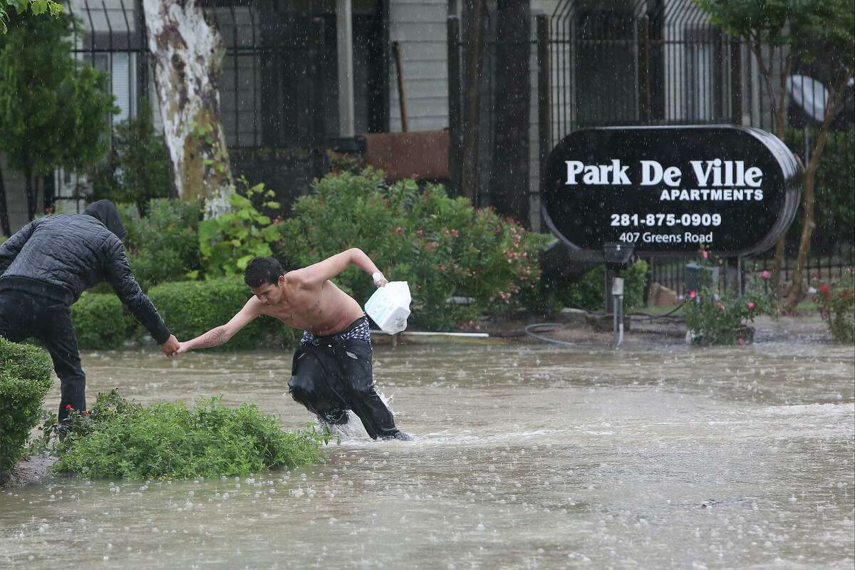 A man helps another from high water near Greens Bayou and Greens Rd. Monday, April 18, 2016, in Houston. ( Steve Gonzales / Houston Chronicle )