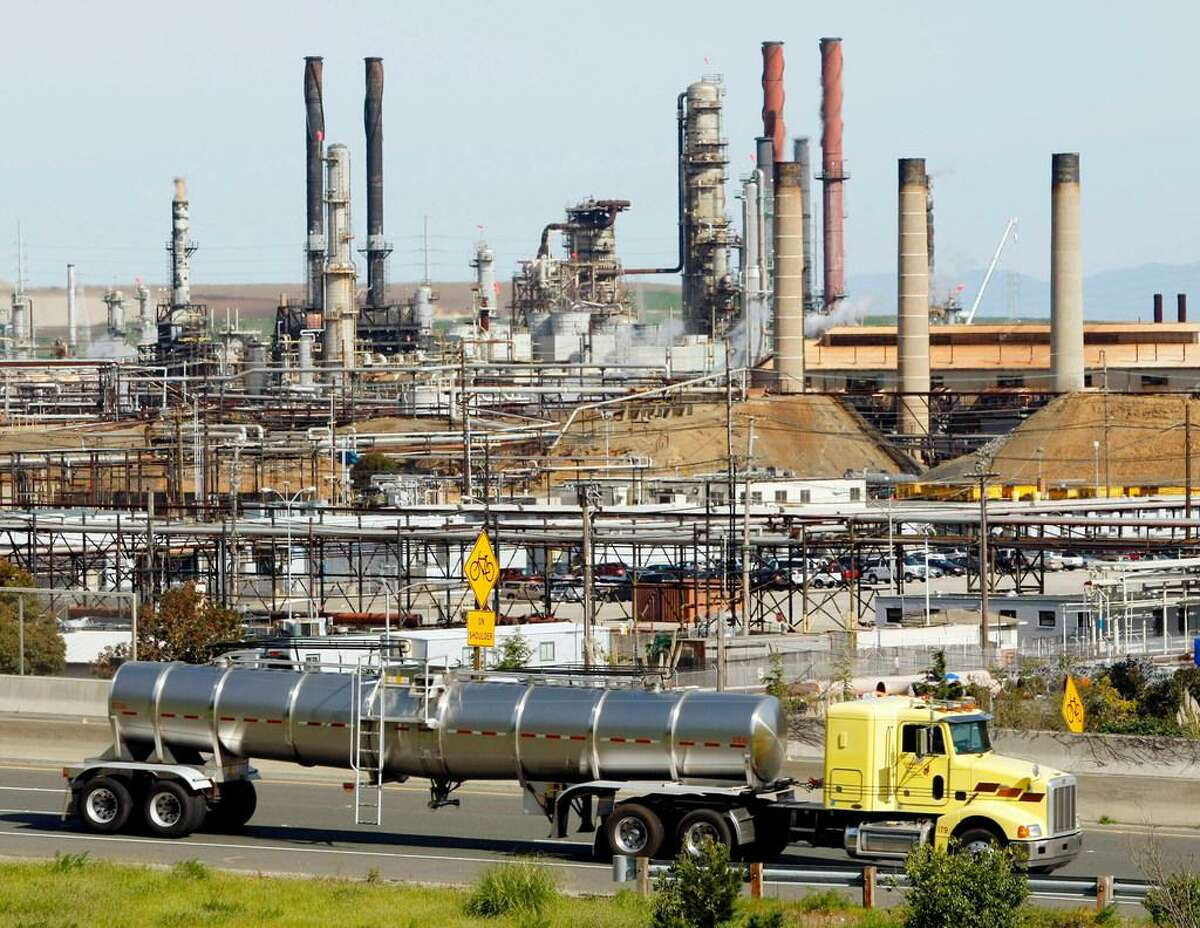 In this March 9, 2010, file photo a tanker truck passes the Chevron oil refinery in Richmond, Calif. A federal appeals court ruled Tuesday, May 26 against major oil companies in lawsuits brought by California cities and counties seeking damages for the impact of climate change.