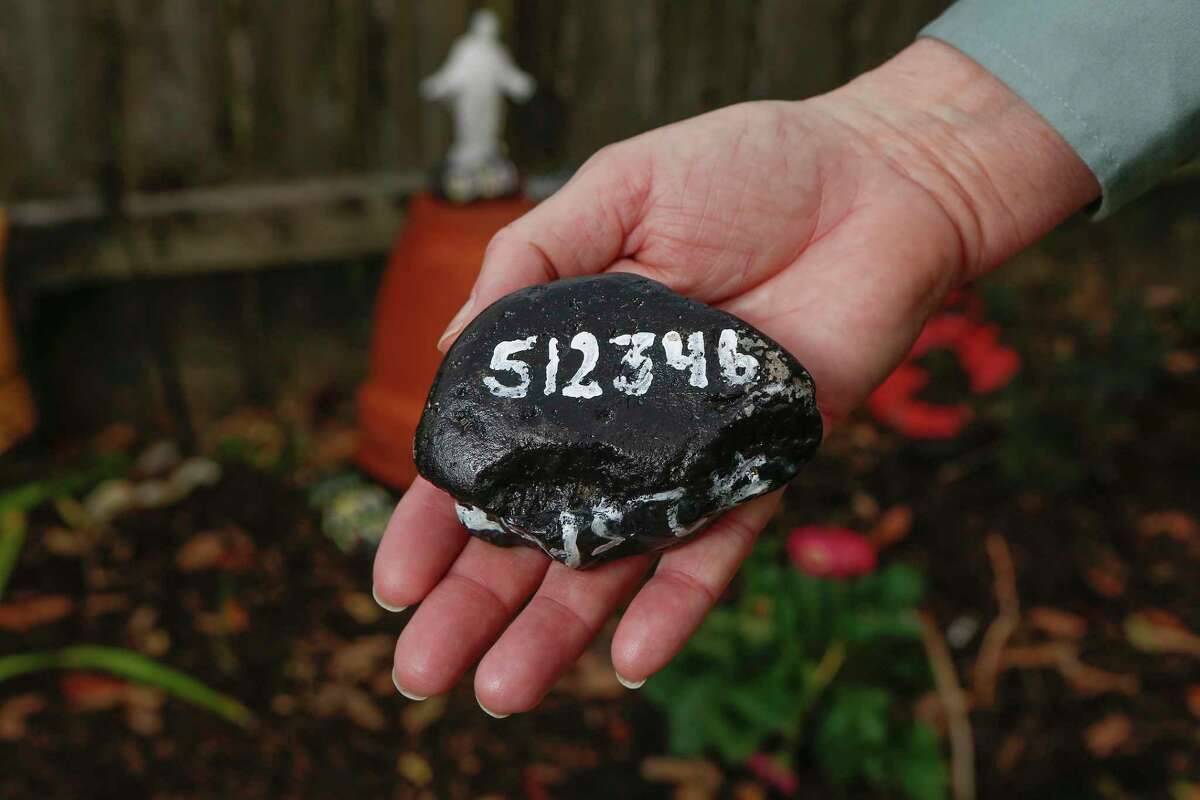 Each of Sandra Dwyer's 12 garden stones is painted with that month's COVID-19 death toll.