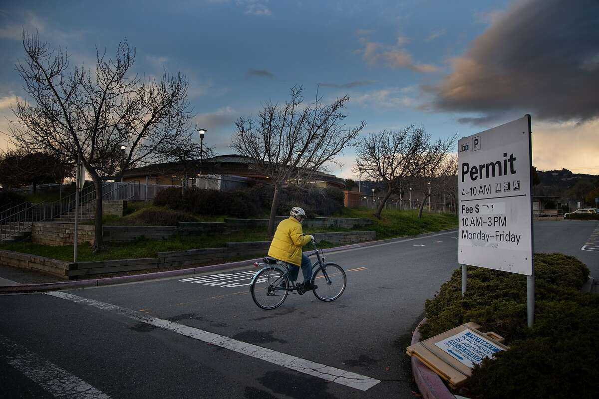 A bicyclist rides near the North Berkeley BART parking lot, a planned site of a future social housing which will create units in buildings for people of varying incomes.