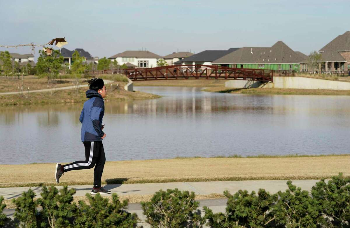 A runner passes by the 25-acre lake at Dragonfly Park in Bridgeland, Houston's most active community for home starts in 2020.