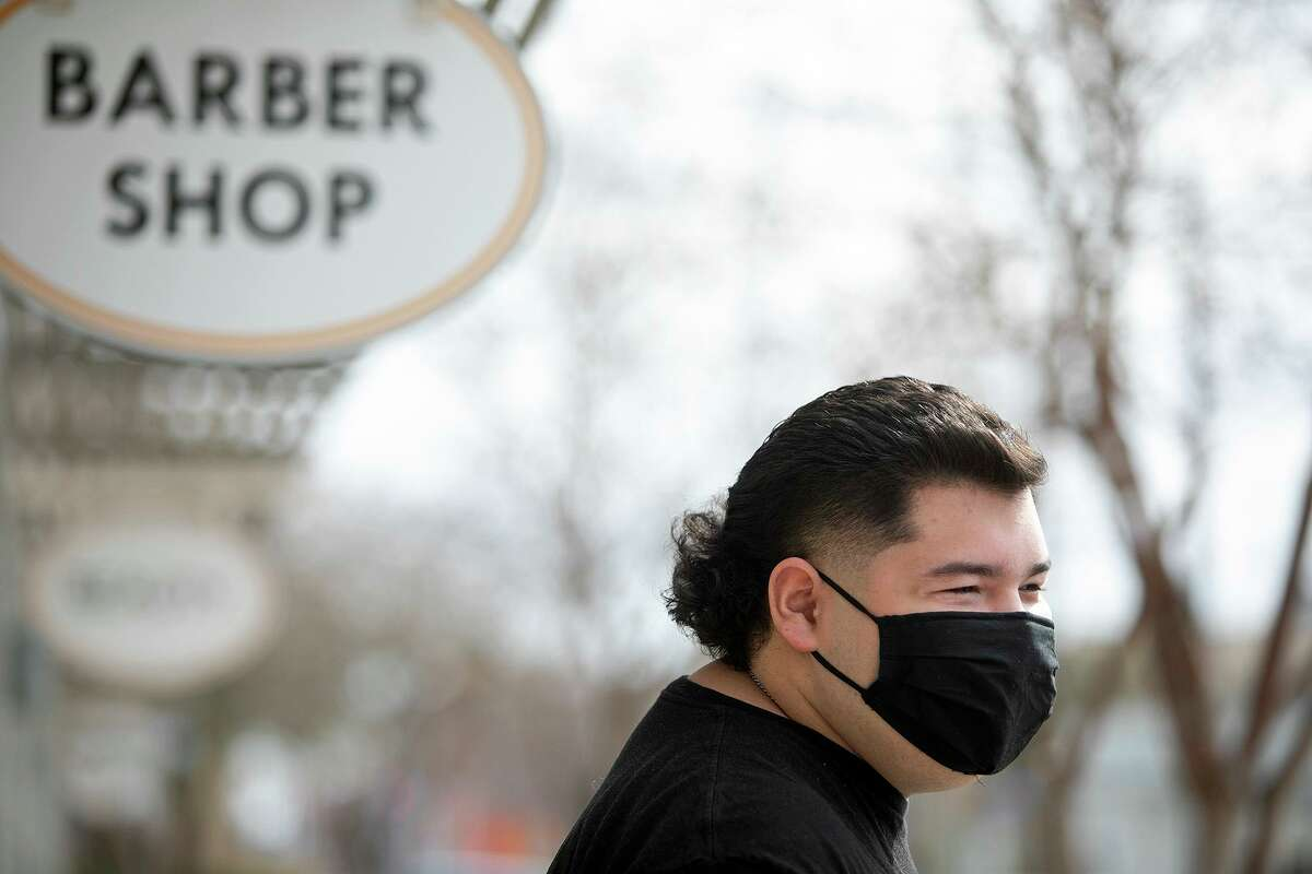 Cristian Muñiz's stands outside Pinstripes Classic Barber Shop after his haircut in San Antonio Thursday.
