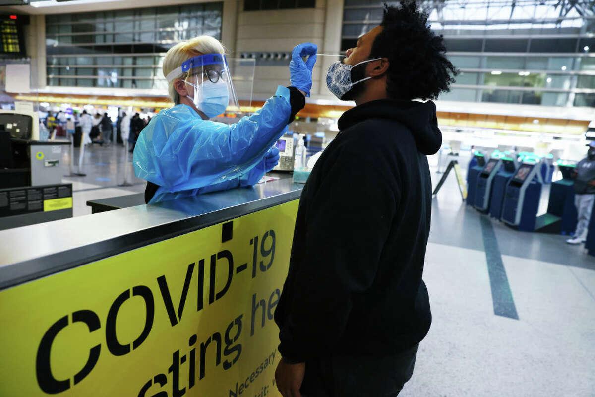 A man receives a nasal swab COVID-19 test at Tom Bradley International Terminal at Los Angeles International Airport (LAX).