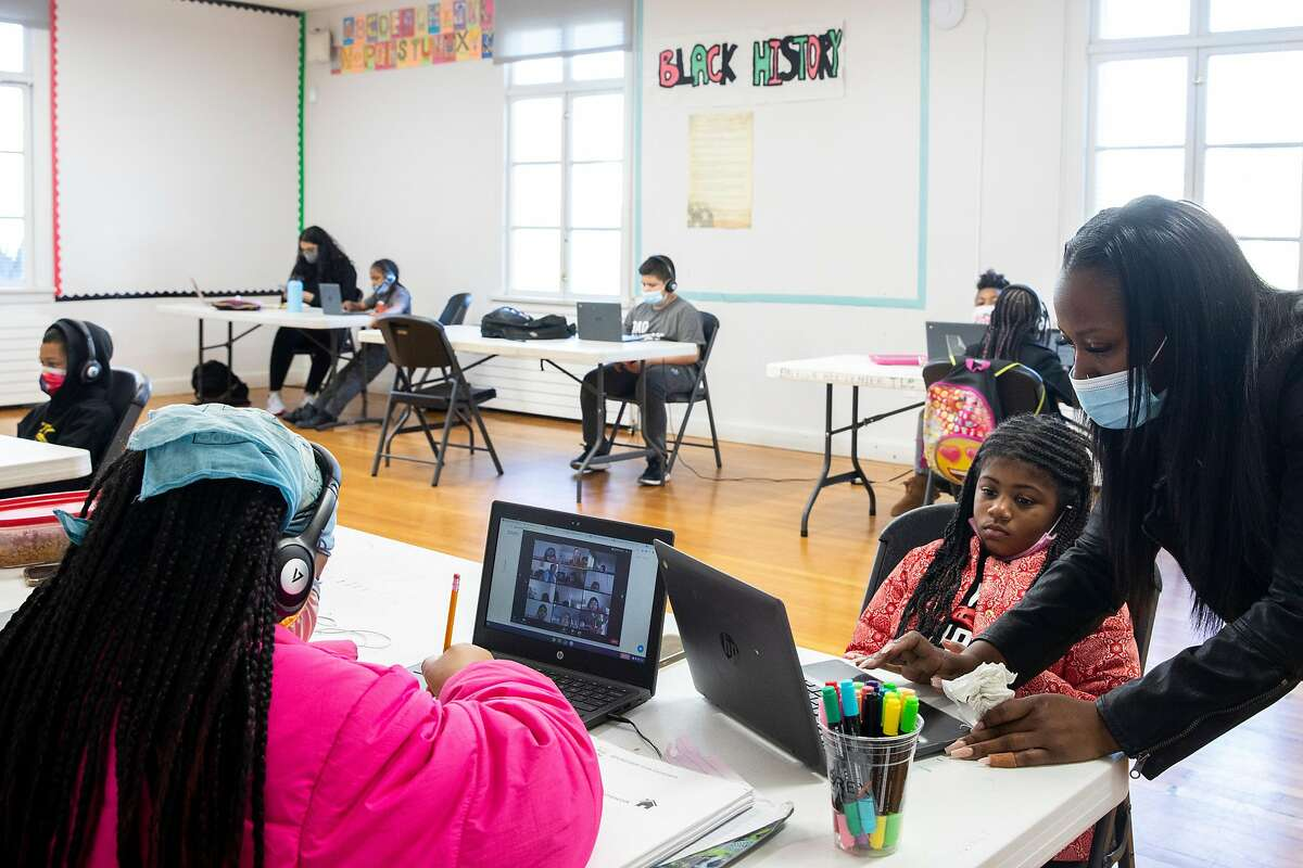 Recreation Leader Kanisha Burdeen (right) assists Skylour Jackson, 7, with her second grade school work while attending Zoom class at Palega Community Learning Hub in February. The district is looking at summer and other supplemental programs to help kids with learning loss due to the pandemic.