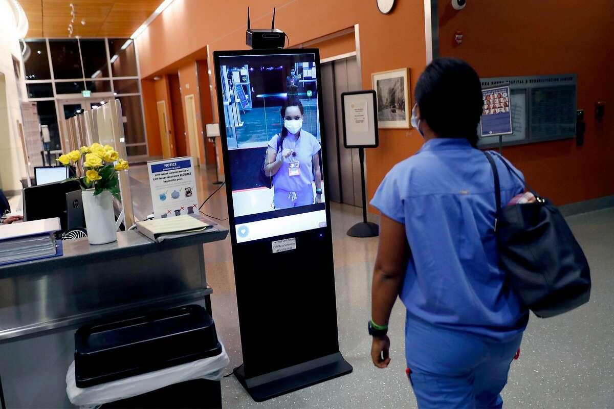 Nurse Beza Kinefe has her temperature checked as she arrives for the night shift at Laguna Honda Hospital.