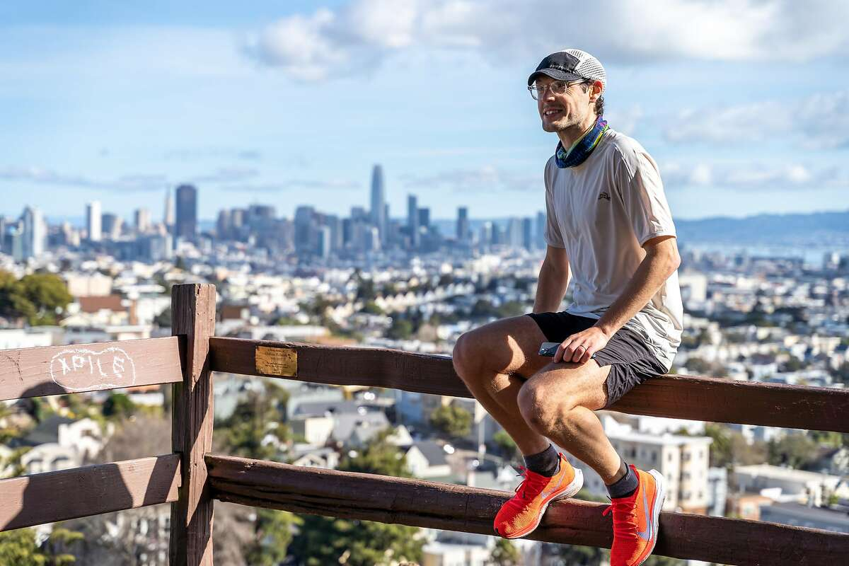Ultrarunner Luke Wicker rests with a view of downtown San Francisco, during his March 6, 2021, run that covered 76 of the city's peaks. He ran 65 miles and climbed more than 10,000 feet.