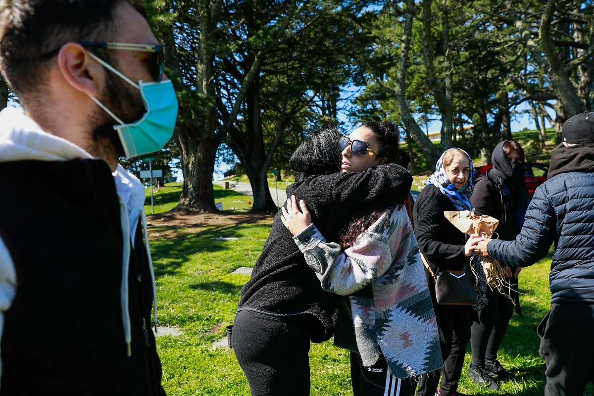 Dima Bsisso (center) is embraced by a friend as she visits the gravesite of her father Sami Bsisso who died of COVID-19 on Friday, March 12, 2021 in San Mateo, California. Sami Bsisso was a longtime beloved owner of Noe Hill Market and was a neighborhood fixture in the Castro for decades. His death is shaking the community.