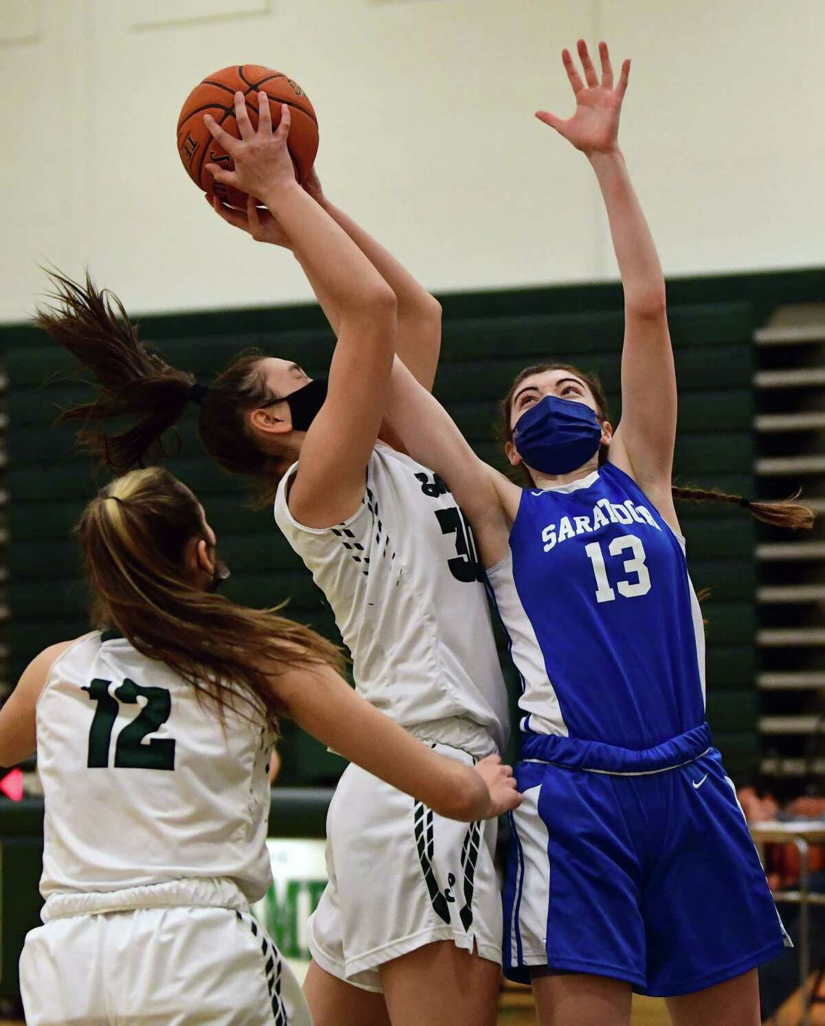 Shenendehowa's Sam Lee and Saratoga's Nora Carminucci battle for a rebound during a basketball game on Friday, March 12, 2021 in Clifton Park, N.Y. (Lori Van Buren/Times Union)
