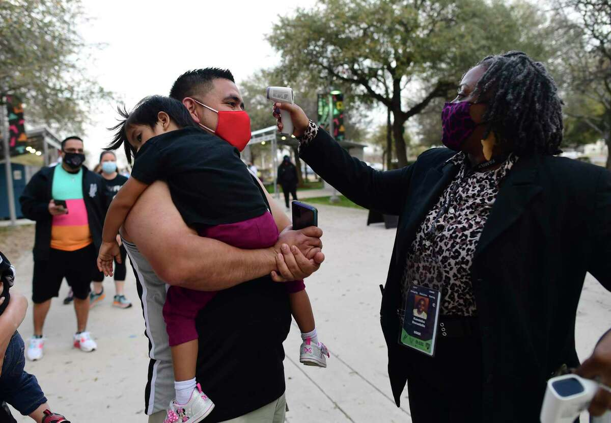 """Bruce Alvarado has his temperature checked as he holds his daughter, Penelope, as they enter AT&T Center for the Spurs' """"Welcome Home Game,"""" the first game in more than a year with fans allowed to attend, albeit with rules and restrictions."""