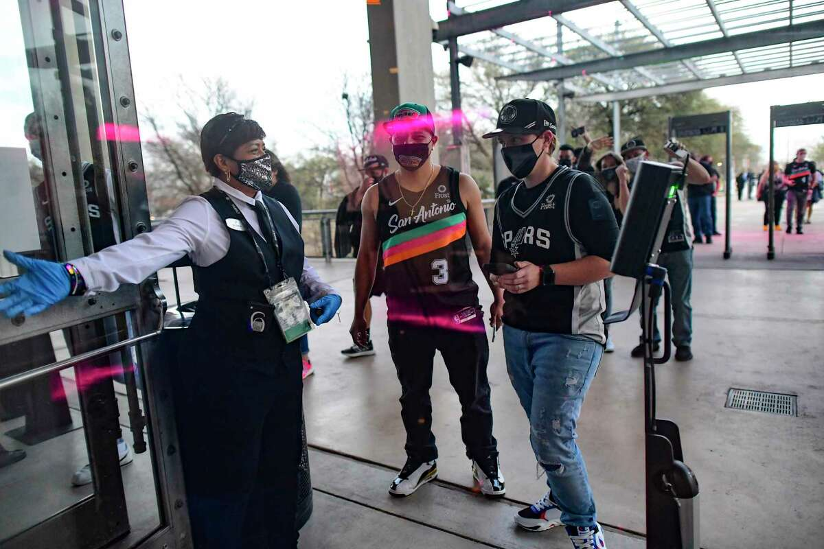 """Fans of the San Antonio Spurs prepare to enter the AT&T Center for the team's """"Welcome Home Game,"""" the first game since March 10, 2020 where fans are allowed to attend. The coronavirus pandemic, up until now, has closed the team's games to the public."""