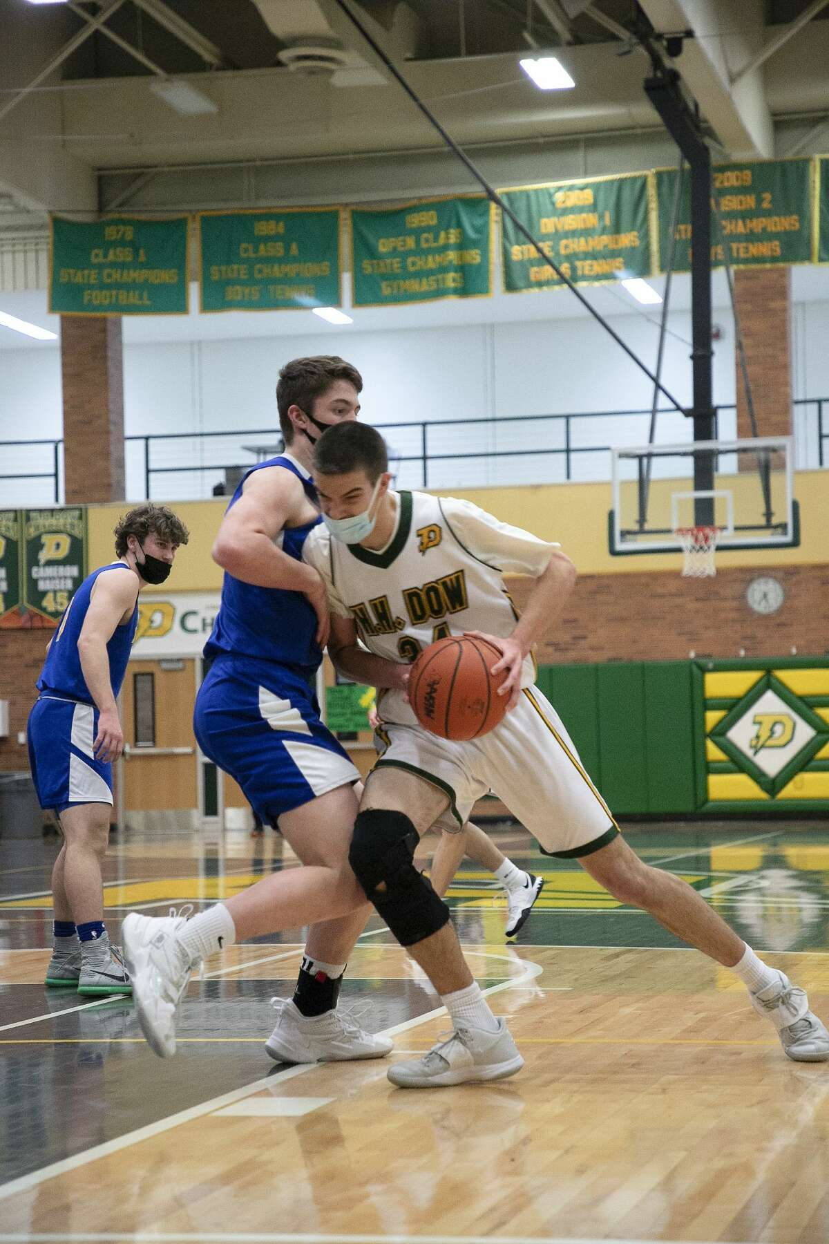 Dow's Nolan Fisher dribbles down the court during a game against Midland Friday, March 12, 2021 at H. H. Dow High School. (Doug Julian/for the Daily News)
