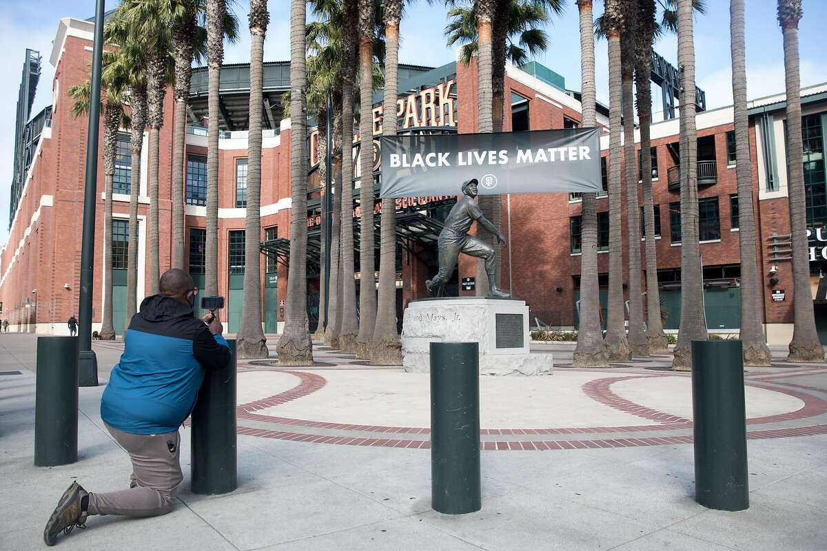 Giants fan Cornelius Miller take a photo of the Willie Mays statue in front of Oracle Park. The San Francisco Giants took on the San Diego Padres for their home opener in San Francisco on July 28, 2020.