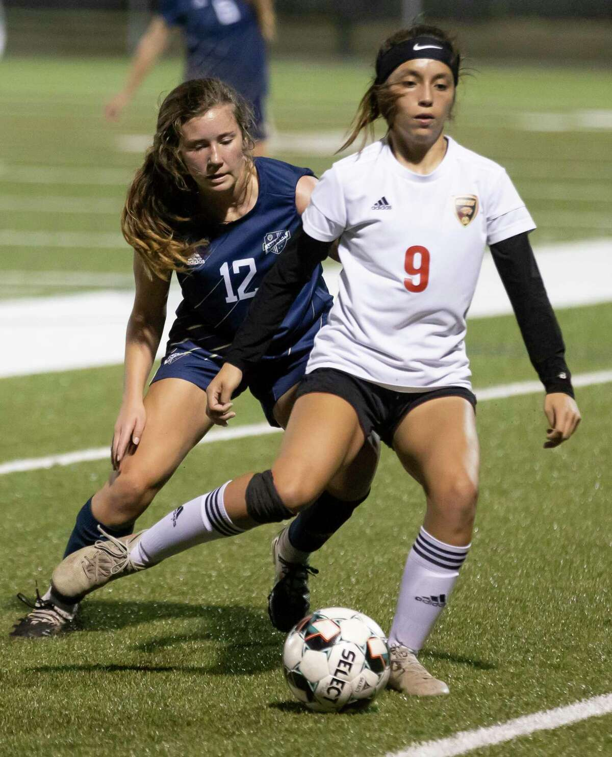 Caney Creek Elyn Zamudio (9) takes control of a throw in while under pressure from Lake Creek Kate Coleman (12) during the first half of a District 20-5A girls soccer game at Lake Creek High School, Friday, March 12, 2021, in Montgomery.