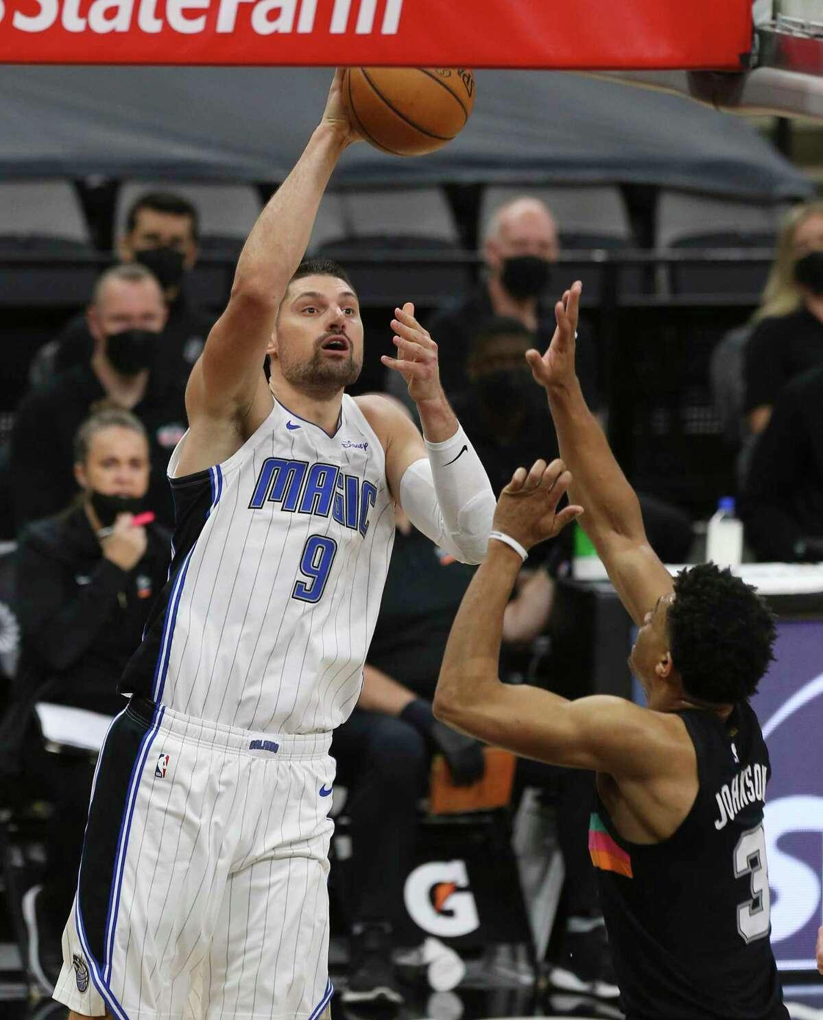 Orlando Magic's Nikola Vucevic (09) scores against Spurs' Keldon Johnson (03) at the AT&T Center on Friday, Mar. 12, 2021.