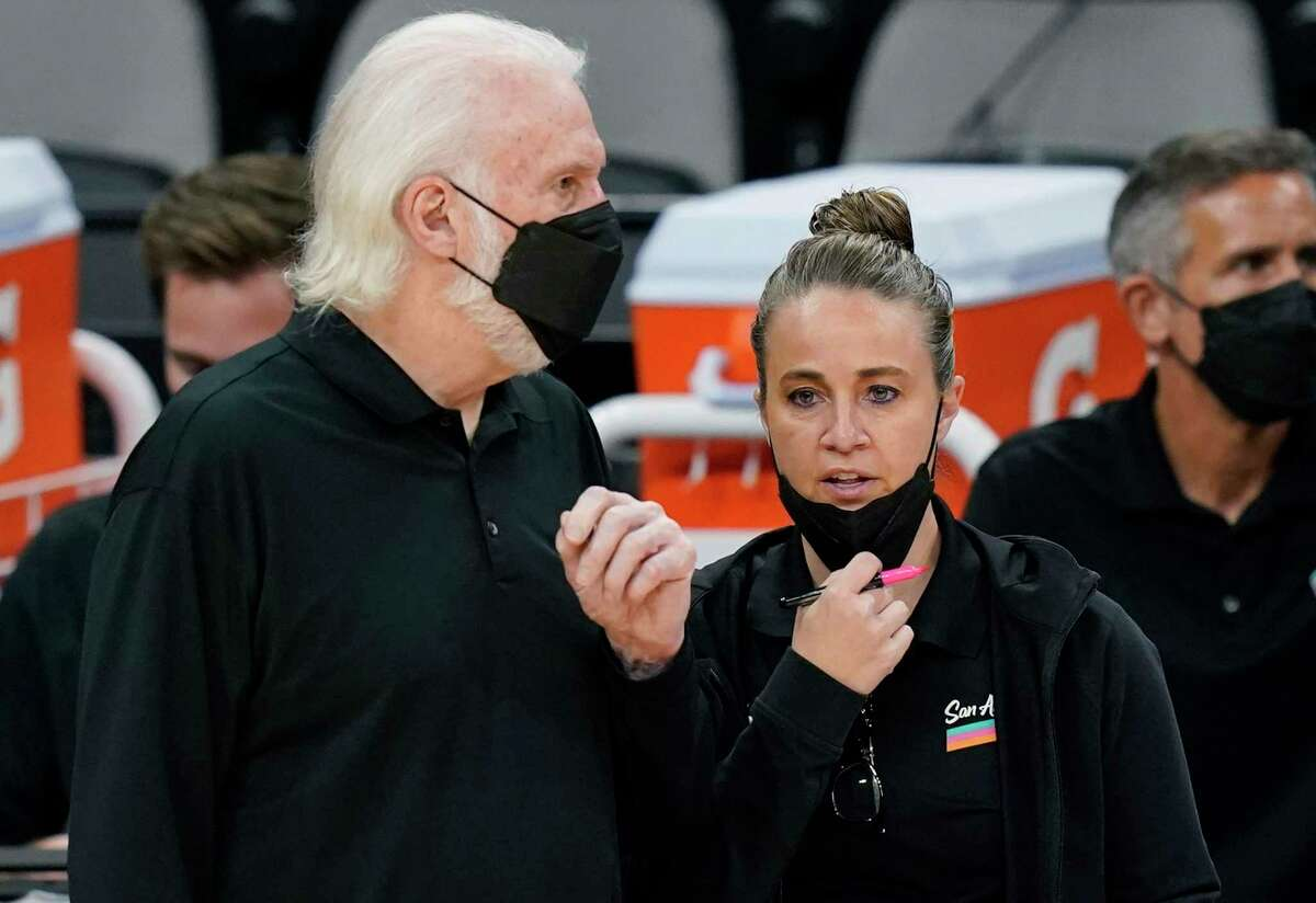 San Antonio Spurs head coach Gregg Popovich, left, talks with assistant coach Becky Hammon, right, during the second half of an NBA basketball game against the Orlando Magic in San Antonio, Friday, March 12, 2021. (AP Photo/Eric Gay)