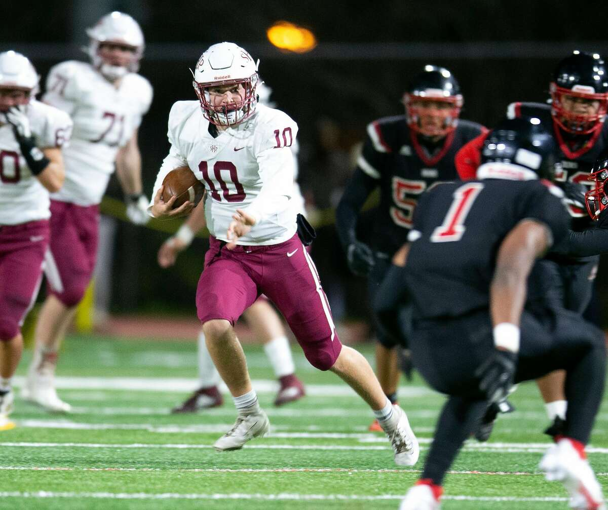 Sacred Heart quarterback Teddy Purcell (10) scrambles away from pressure during the first half of a high school football game against Aragon on Friday.