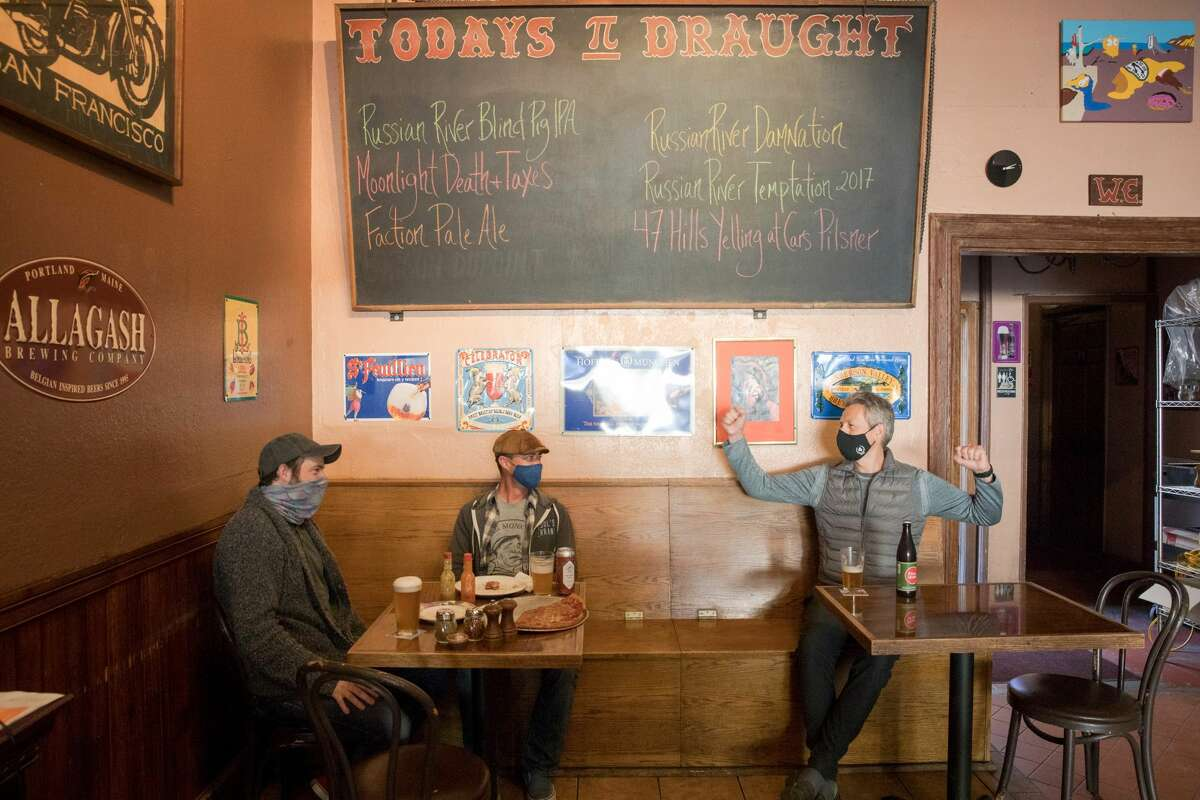 """Left to right, Joe Gallagher, Nelson """"Just Nelson"""" and James Field share some food dining inside at the Pi Bar in San Francisco on March 12, 2021."""