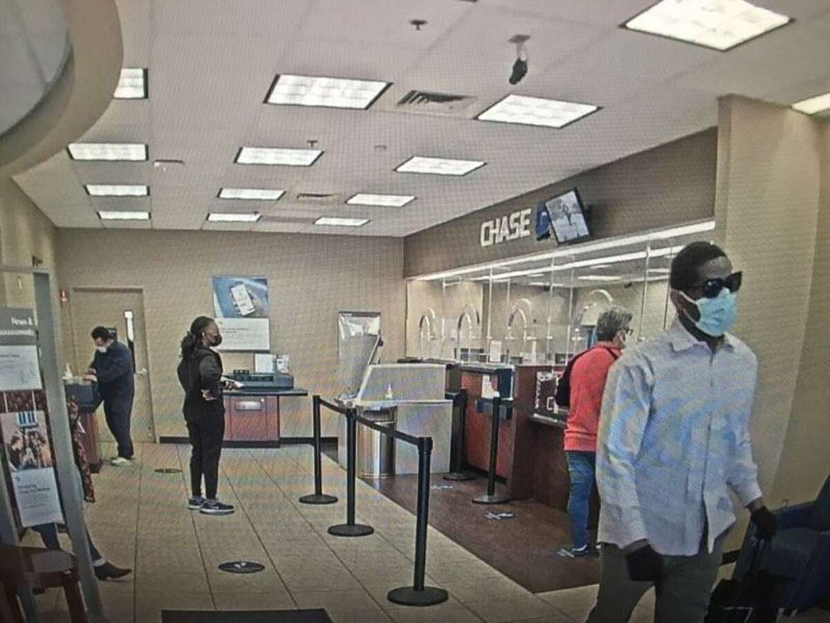 Surveillance camera footage shows a robbery suspect at the Main Street Chase Bank approaching a customer service counter, displaying a note and leaving with a black tote bag.