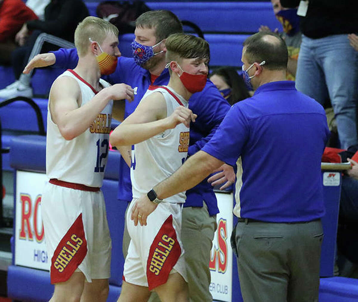 Roxana seniors Cade Slayden (left) and Austin Martin are greeted at the bench by assistant Jerry Wheaton and head coach Mark Briggs (right) after leaving the court for the final time Friday night at Larry Milazzo Gym in Roxana.