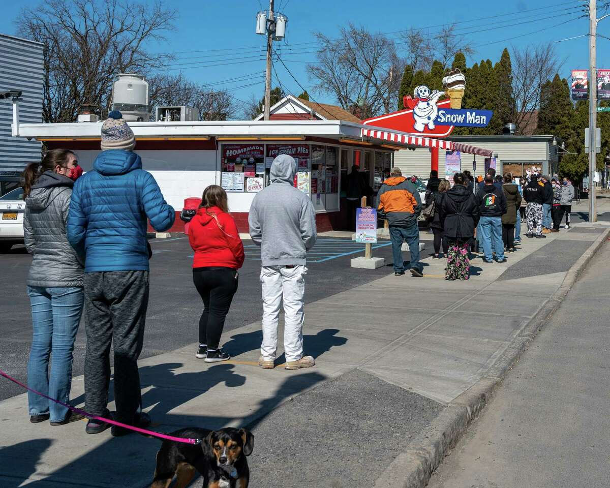 A long line of people wait for ice cream and other goodies during opening day of the Snowman on Fifth Avenue in Troy, NY, on Saturday, March 13, 2021 (Jim Franco/special to the Times Union.)