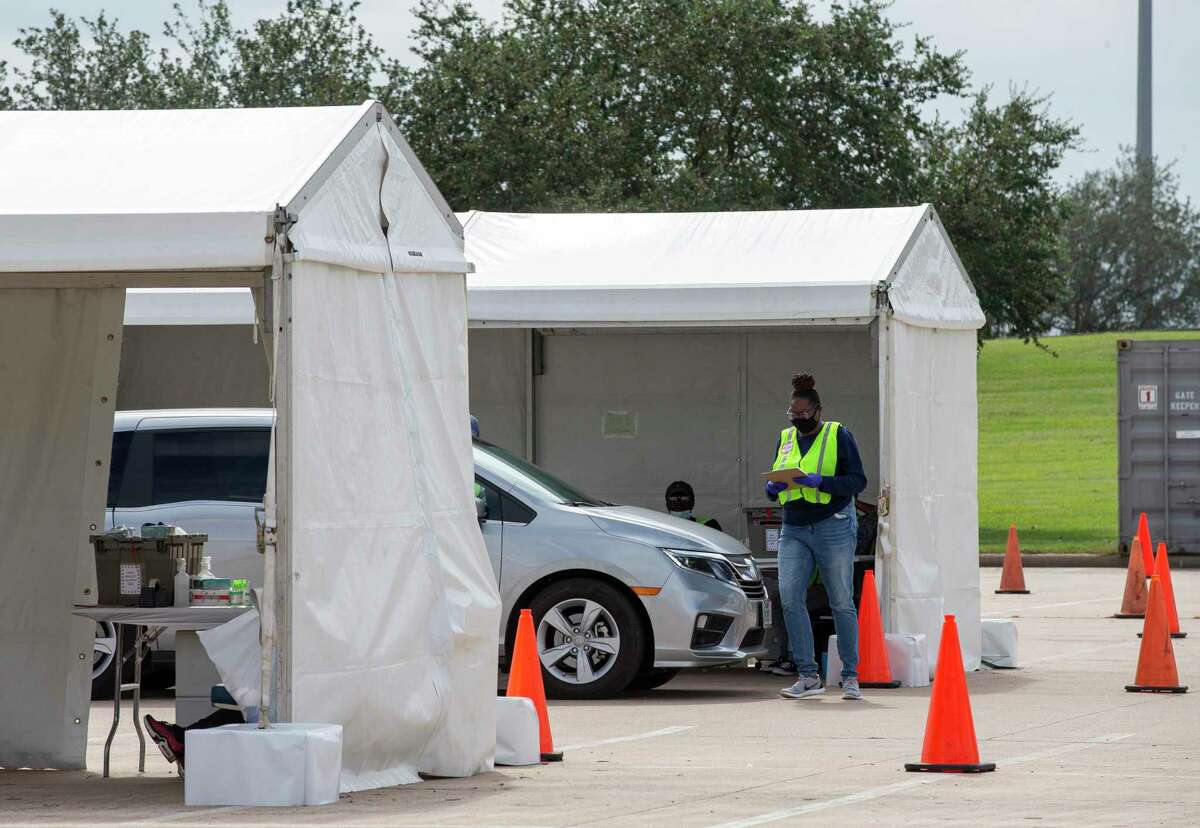 A Harris County staff member assists a voter at a drive-thru at NRG Arena on Oct. 17.