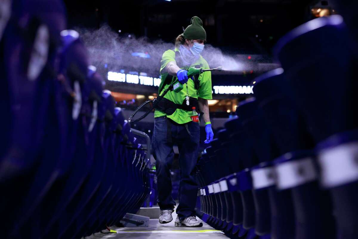A Lucas Oil Stadium employee disinfects the the seats due to Covid-19 after the game between Purdue and Ohio State on Friday. The stadium will host NCAA Tournament games later this month.