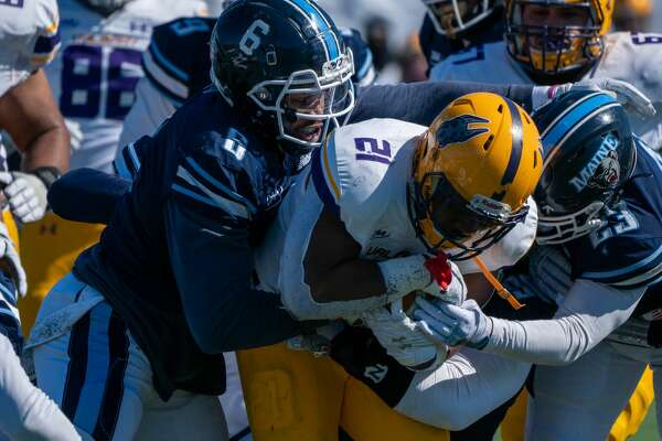 UAlbany running back Karl Mofor power through Maine defenders Deshawn Stevens (6) and Adrian Otero in a Colonial Athletic Association football game Satureay, May 13, 2021, at Orono, Maine. Mofor rushed for 155 yards on 30 carries, but the UAlbany lost the game, 38-34. (Ronald Gillis/Maine athletics)