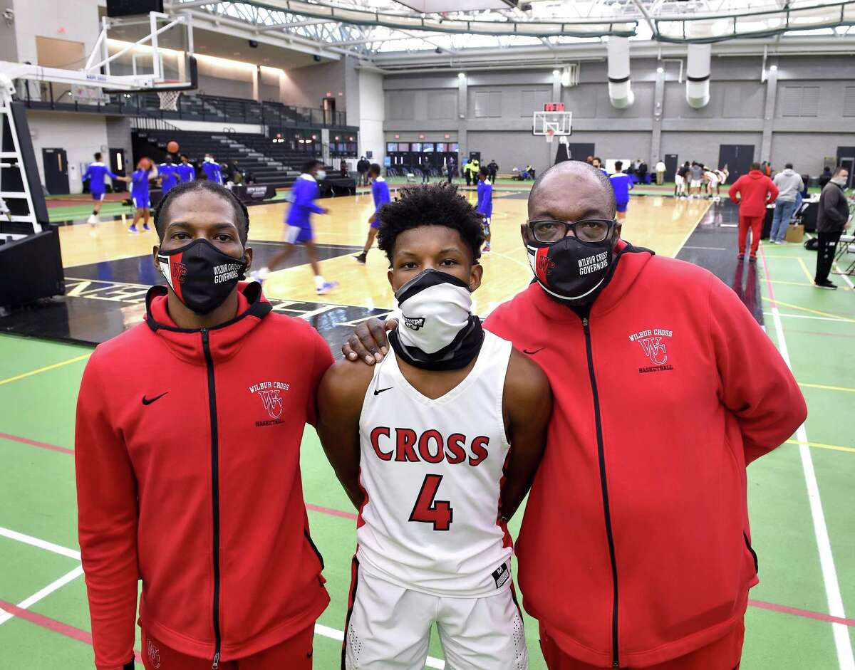 Wilbur Cross boys basketball assistant coach Gerald McClease, Sr. (right), is photographed with his son, Gerald McClease, Jr. (left) and grandson, Christian McClease (center), before a game at the Floyd Little Athletic Center in New Haven on March 6, 2021.