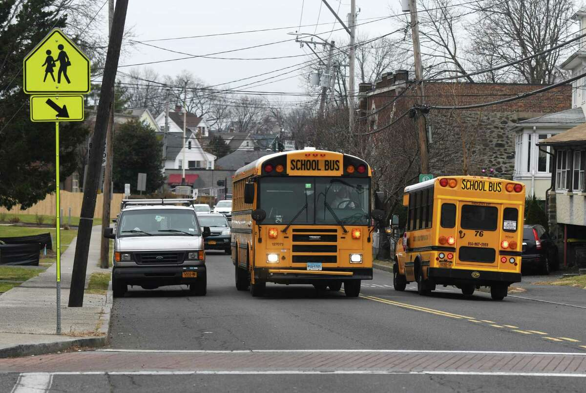 School buses pass the sidewalk at the intersection of Delavan Avenue and New Lebanon Avenue after the dismissal of New Lebanon School in the Byram section of Greenwich, Conn. Tuesday, Jan. 14, 2020.