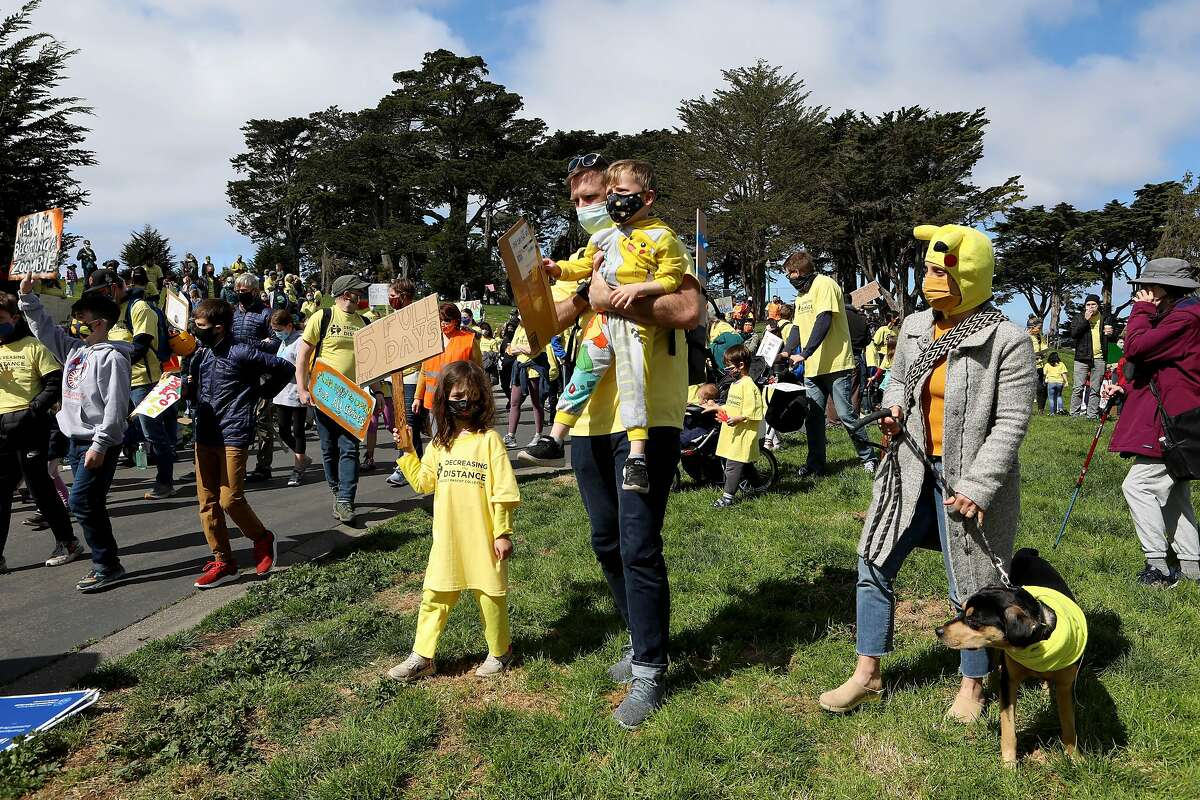 """Maya Sears, 6, holds a sign stating """"Five full days"""" as she stands next to her father Dave Sears, as he holds her brother Llewyn Sears, 3, with mother Kari Sears holding their dog during a rally on March 13 to demand schools fully reopen in San Francisco."""