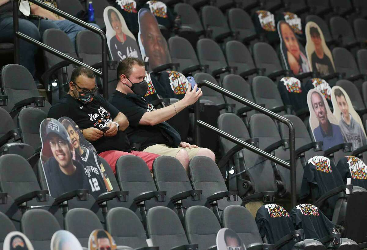 Fans record their attendance at the Spurs game against the Orlando Magic at the AT&T Center on Friday, Mar. 12, 2021. The game was the first time fans were allowed to watch a game in the arena since the start of the Covid-19 pandemic last year.