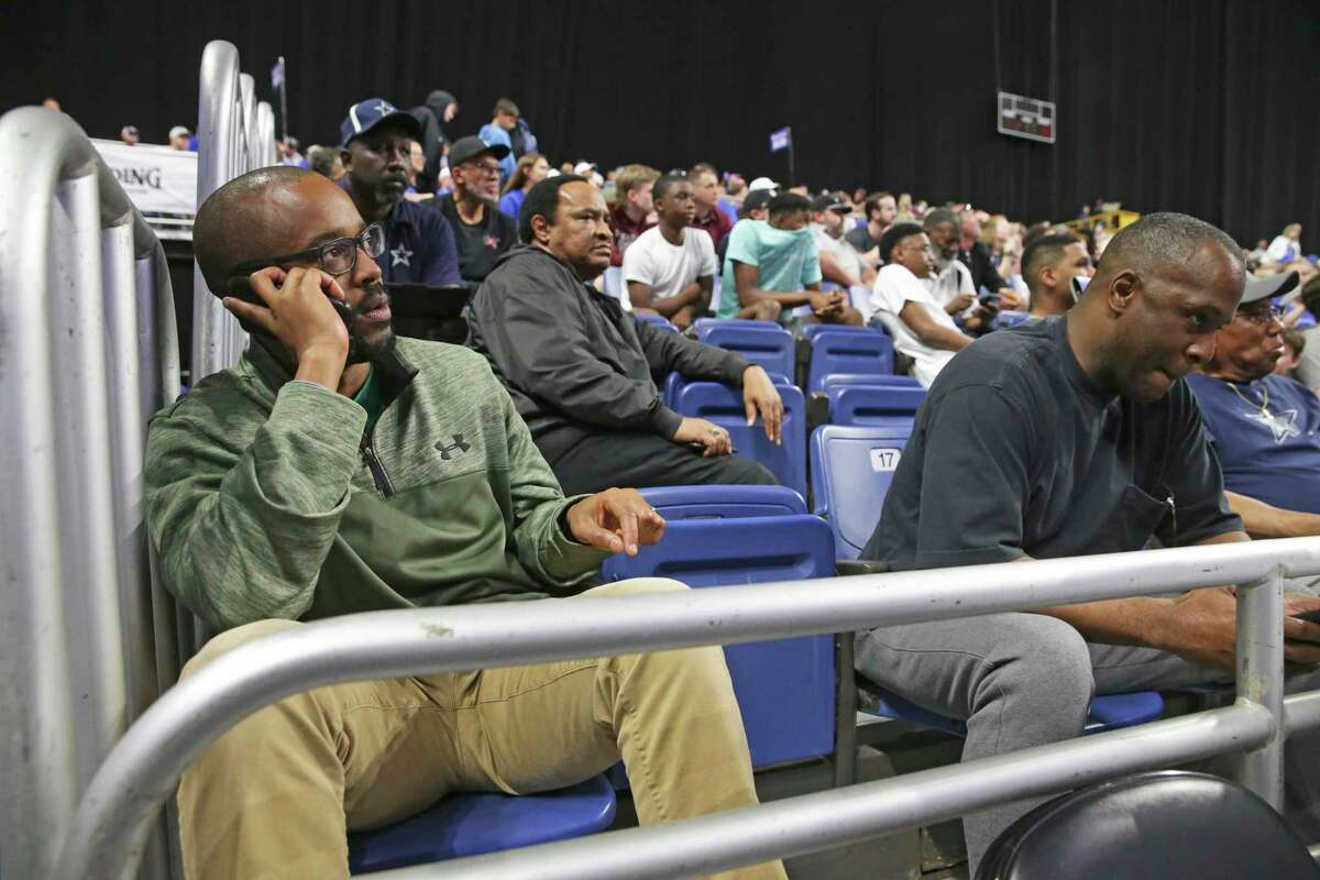 Bobby Clemons, Jr., left, from Austin makes arrangements for his return trip home just before the class 3A state semifinal boys basketball game between Cole and Peaster at the Alamodome on Feb. 12, 2020. Mark Ervin, right, from Columbus, Ohio already had made plans to go home in response to the suspension of games at the UIL.