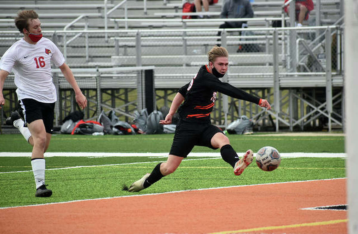 Edwardsville's Brendan James, right, blasts a left-footed shot just wide of the goal in the first half against Alton inside the District 7 Sports Complex in Edwardsville.